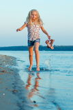 Muchacha que corre en la playa en el agua descalzo Fotografía de archivo