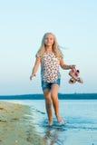 Muchacha que corre en la playa en el agua descalzo Imagenes de archivo