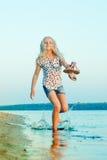 Muchacha que corre en la playa en el agua descalzo Imagen de archivo libre de regalías