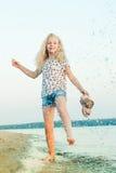 Muchacha que corre en la playa en el agua descalzo Foto de archivo