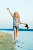 Muchacha que corre en la playa en el agua descalzo Foto de archivo libre de regalías