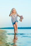 Muchacha que corre en la playa en el agua descalzo Imágenes de archivo libres de regalías