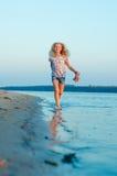 Muchacha que corre en la playa en el agua descalzo Imagen de archivo