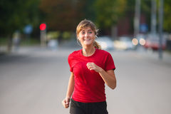 Muchacha que corre en una ciudad Fotos de archivo libres de regalías