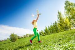 Muchacha que corre rápidamente y que sostiene el juguete del aeroplano Fotos de archivo libres de regalías
