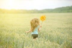 Muchacha que corre a través de campo con el molinillo de viento Foto de archivo