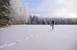 Muchacha que corre a través del campo de nieve Imagenes de archivo
