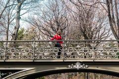 Muchacha que cruza un puente en el Central Park en ci de Manhattan, Nueva York Foto de archivo libre de regalías