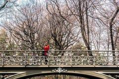 Muchacha que cruza un puente en el Central Park en ci de Manhattan, Nueva York Imagen de archivo