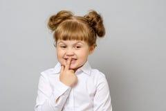 Muchacha que cubre su boca con su finger foto de archivo
