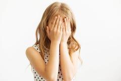 Muchacha que cubre su cara con sus manos foto de archivo