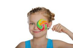 Muchacha que cubre su caramelo del ojo Fotografía de archivo