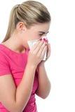 Muchacha que cubre su nariz con el pañuelo mientras que estornuda Fotografía de archivo