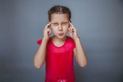 Muchacha que cubre sus oídos y ojos en un vestido rojo encendido Imagen de archivo libre de regalías