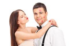 Muchacha que cubre a un hombre joven en besos Fotografía de archivo