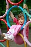Muchacha que cuelga en los anillos un patio de los niños Imagenes de archivo