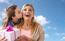 Muchacha que da el presente de cumpleaños a la madre sobre el cielo Imagenes de archivo