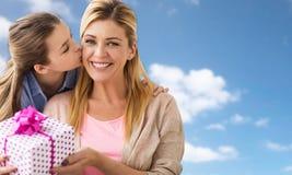 Muchacha que da el presente de cumpleaños a la madre sobre el cielo Fotos de archivo