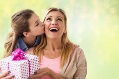 Muchacha que da el presente de cumpleaños a la madre sobre luces Foto de archivo
