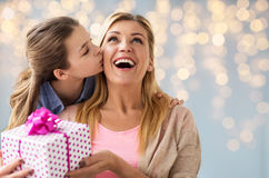 Muchacha que da el presente de cumpleaños a la madre sobre luces Foto de archivo libre de regalías