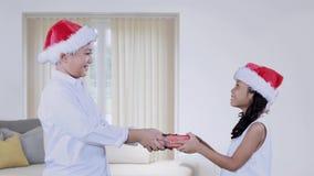 Muchacha que da el regalo de la Navidad a su hermano en casa almacen de video
