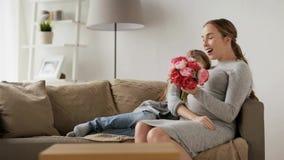 Muchacha que da las flores a su madre embarazada en casa almacen de video