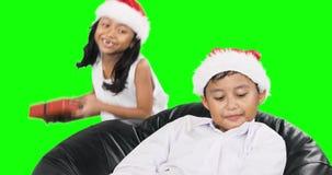 Muchacha que da a su hermano un regalo de la Navidad almacen de metraje de vídeo