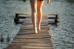 Muchacha que da un paseo a lo largo de un embarcadero en la charca en puesta del sol Foto de archivo libre de regalías
