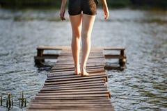 Muchacha que da un paseo a lo largo de un embarcadero en la charca en puesta del sol Fotografía de archivo libre de regalías