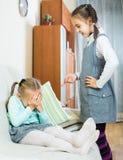 Muchacha que da una conferencia a la pequeña hermana en interior nacional foto de archivo libre de regalías