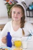 Muchacha que desayuna en cocina Imágenes de archivo libres de regalías