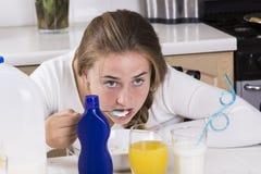 Muchacha que desayuna en cocina Foto de archivo libre de regalías