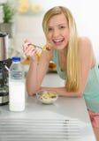 Muchacha que desayuna que come escamas con leche Imagen de archivo libre de regalías