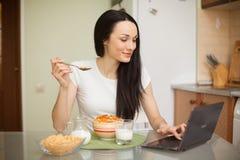 Muchacha que desayuna y que usa su ordenador portátil en la cocina Imagen de archivo libre de regalías