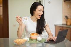 Muchacha que desayuna y que usa su ordenador portátil en la cocina Foto de archivo