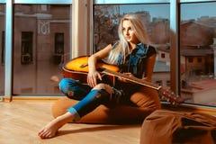 Muchacha que descansa con una guitarra en sus manos cerca de las ventanas grandes w Imágenes de archivo libres de regalías