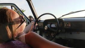 Muchacha que descansa en coche en el cielo azul del fondo, femenino en contraluz en el coche, mujer joven que se sienta en el coc almacen de metraje de vídeo