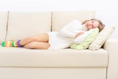 Muchacha que descansa sobre el sofá Fotos de archivo libres de regalías