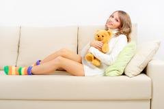 Muchacha que descansa sobre el sofá Fotografía de archivo