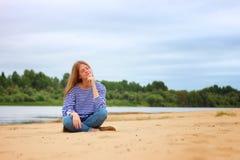 Muchacha que descansa sobre la playa, en los bancos del río Foto de archivo