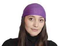 Muchacha que desgasta pañuelo púrpura en el fondo blanco Imagen de archivo