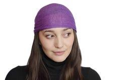 Muchacha que desgasta pañuelo púrpura en el fondo blanco Imagenes de archivo