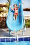 Muchacha que desliza abajo la diapositiva de agua. Imágenes de archivo libres de regalías