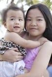Muchacha que detiene al bebé en la ubicación Imagen de archivo