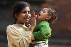 Muchacha que detiene a su pequeña hermana Imagenes de archivo