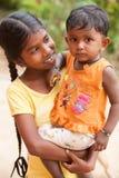 Muchacha que detiene a una hermana más joven en sus brazos foto de archivo