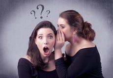 Muchacha que dice cosas secretas a su novia Imagenes de archivo