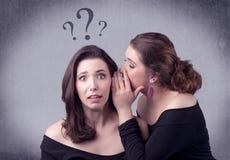 Muchacha que dice cosas secretas a su novia Foto de archivo