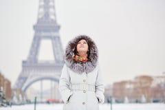 Muchacha que disfruta de día de invierno nevoso raro en París imagenes de archivo