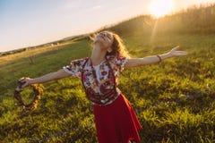 Muchacha que disfruta de la naturaleza en el campo La muchacha es giro alegre con una guirnalda de flores en sus manos Imagen de archivo libre de regalías